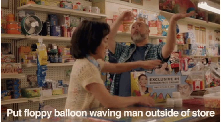 guy telling his wife how he's going to advertise by putting a big waving man outside